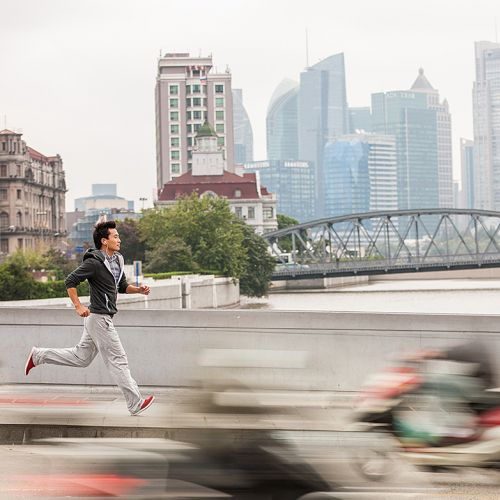 chinese man running in busy city